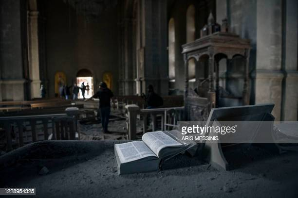 Bible lies open on an altar as journalists report on October 8, 2020 inside the damaged Ghazanchetsots Cathedral in the historic city of Shusha, some...