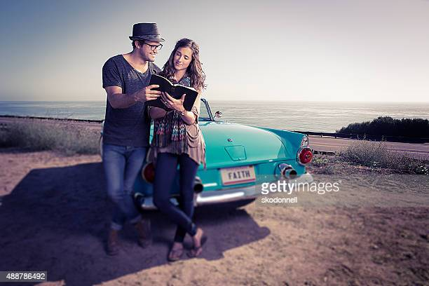 Bible Reading Couple by a Blue Convertible