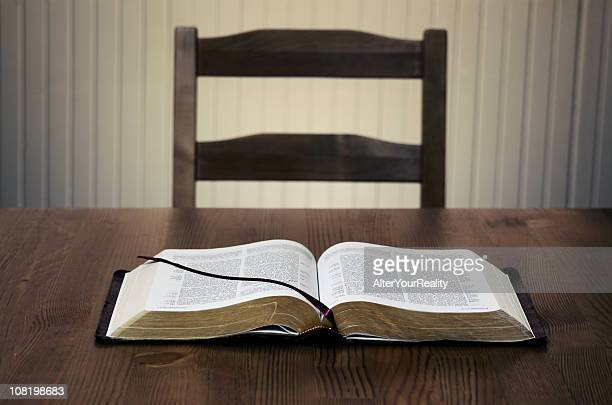 Bible sitting open on a table in front of an empty chair