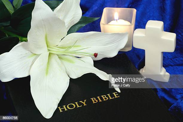 Bible with White Lily, Cross, and Candle on blue