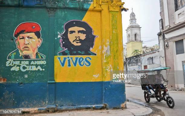 A bicitaxi rides near a graffiti of late Venezuelan president Hugo Chavez and Argentineborn revolutionary leader Ernesto Che Guevara in Havana ahead...