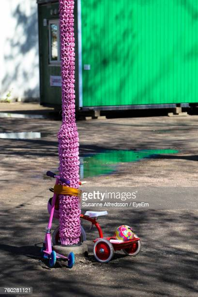 Bicycle And Push Scooter By Crocheted Pole On Footpath