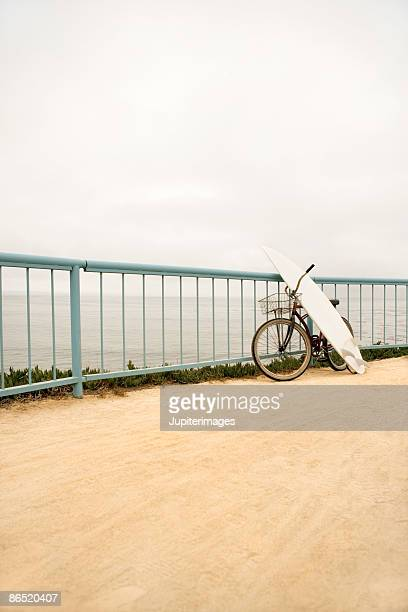 bicycle and surfboard against railing near beach - human powered vehicle fotografías e imágenes de stock