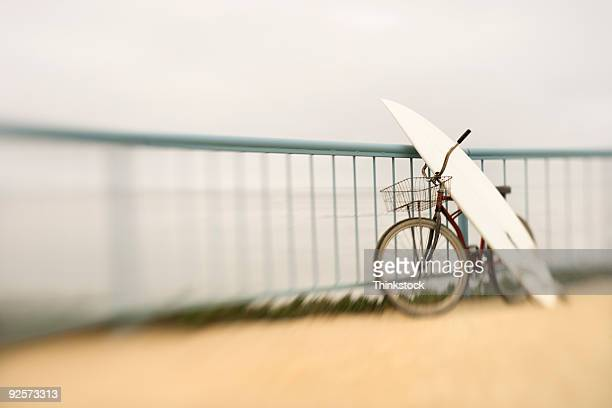 bicycle and surfboard leaning against railing - human powered vehicle fotografías e imágenes de stock