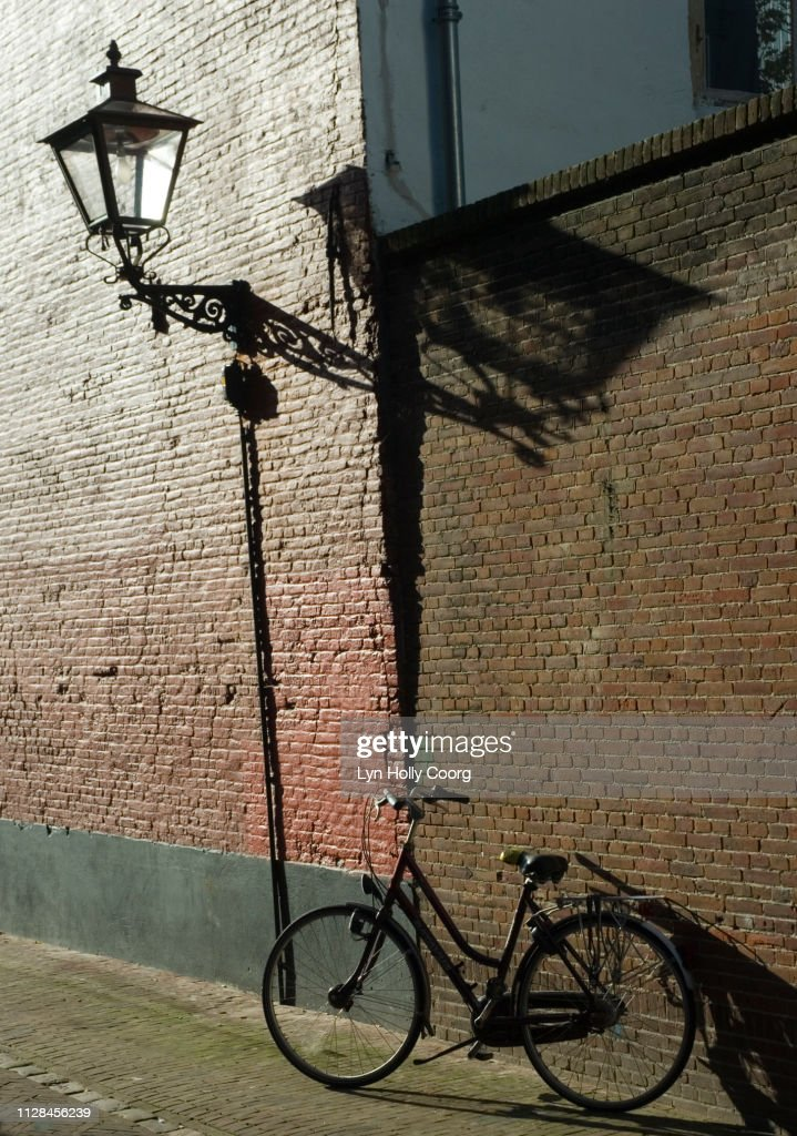Bicycle and wall street light in cobbled street in Leiden Netherlands : Stock Photo