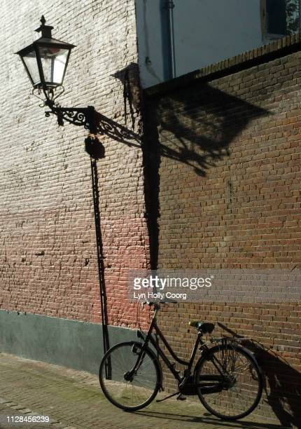 bicycle and wall street light in cobbled street in leiden netherlands - lyn holly coorg stock-fotos und bilder