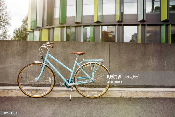 bicycle at a wall in urban surrounding - fahrrad stock-fotos und bilder