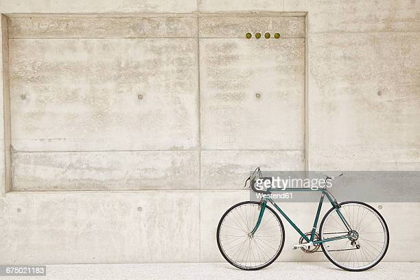 bicycle at concrete wall - fahrrad stock-fotos und bilder