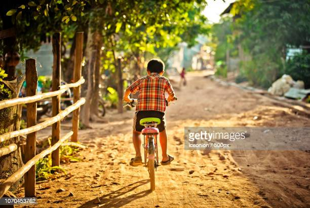 bicycle boy - laotian culture stock pictures, royalty-free photos & images