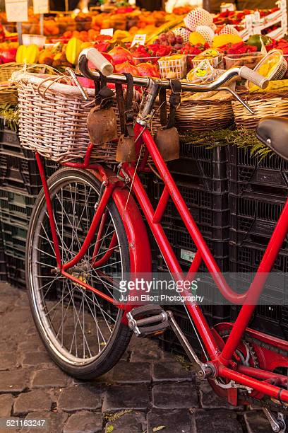 A bicycle by a market stall in Rome.