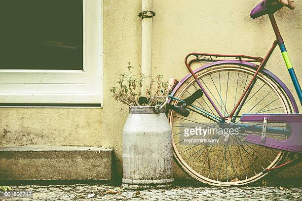 Bicycle chained outside a house next to dairy bucket with flowers