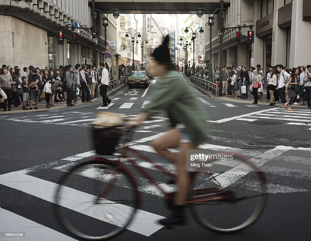 Bicycle commuter passing by a busy pedestrian crossing in Shibuya, Tokyo