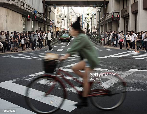 Bicycle commuter passing by a busy pedestrian crossing in Shibuya Tokyo