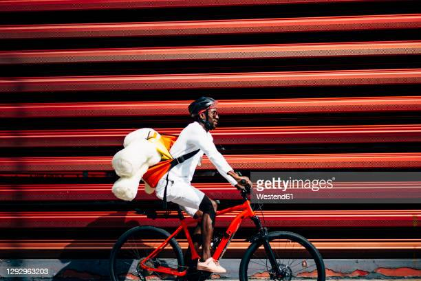 bicycle courier delivering a teddy bear passing a red wall - velo humour photos et images de collection