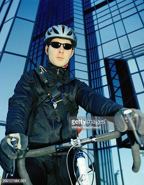 Bicycle courier in front of office building, portrait, low angle view