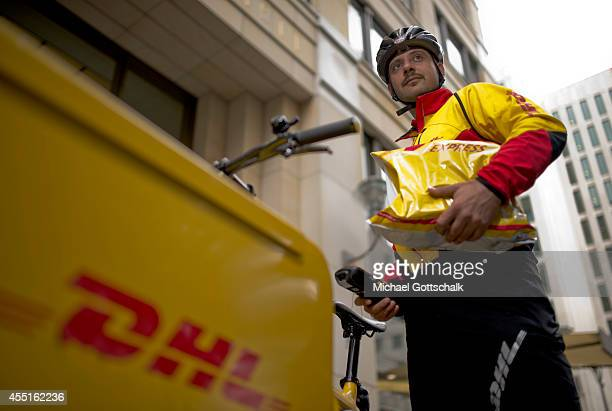 A bicycle courier of german postal service DHL delivers an express package on September 09 2014 in Berlin Germany