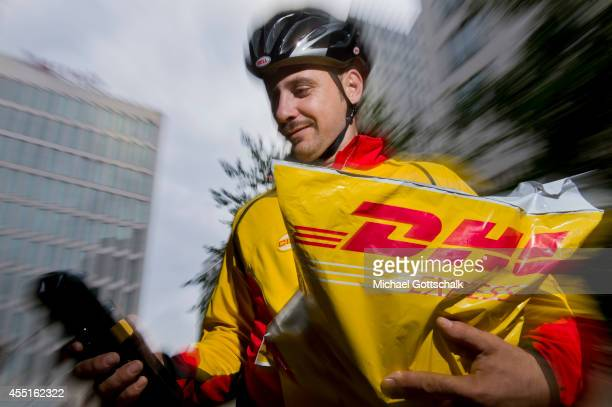 A bicycle courier of german postal service DHL delivers an express consignment on September 09 2014 in Berlin Germany