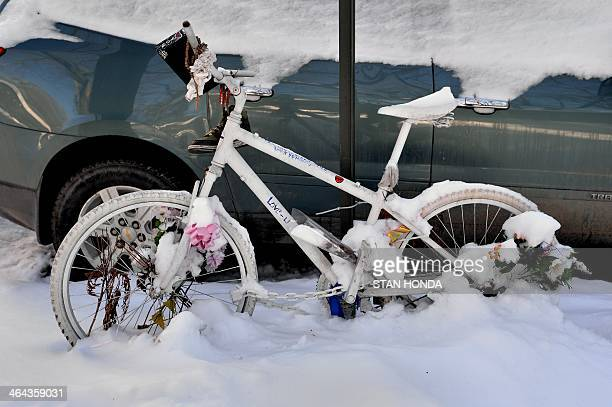 A bicycle decorated with flowers and messages covered with snow on Fifth Avenue January 22 2014 in New York The display is in memory of a cyclist...