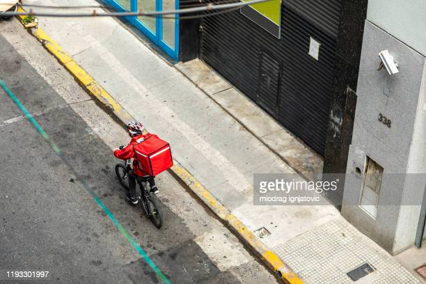 bicycle delivery in the city - drone point of view stock pictures, royalty-free photos & images