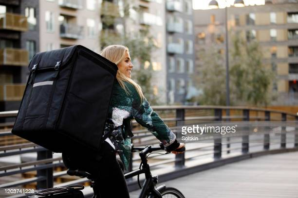 bicycle delivery woman with food backpack cycling in residential area - montare foto e immagini stock