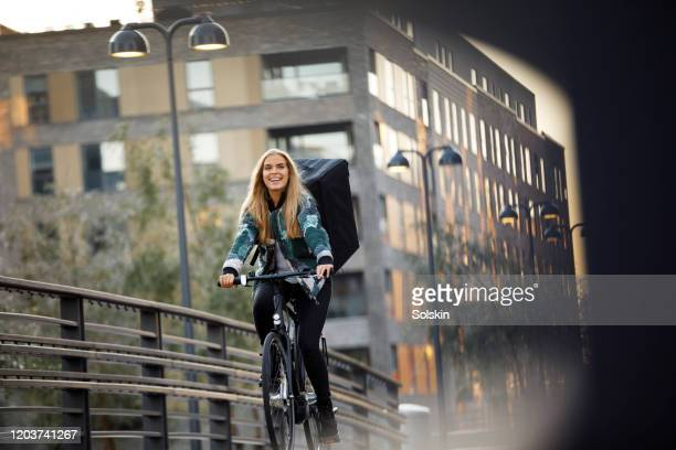 bicycle delivery woman with food backpack cycling in residential area - sustainability stock pictures, royalty-free photos & images