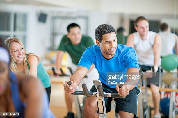 bicycle exercising exercise class - exercise bike stock photos and pictures