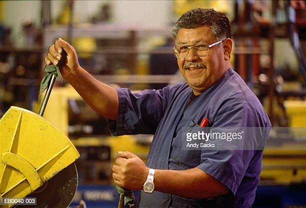 bicycle factory worker cutting tubing with cutoff saw, portrait - southern european descent stock pictures, royalty-free photos & images