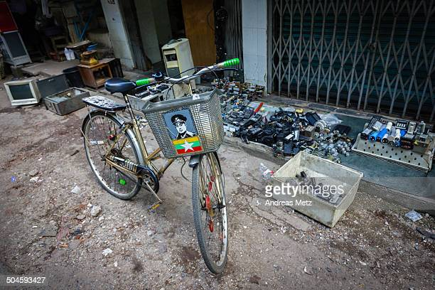 CONTENT] Bicycle featuring the portrait of Myanmar's national hero General Aung San and the Burmese flag in a side street of Yangon