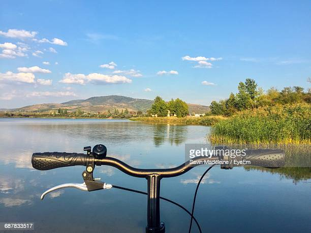 bicycle handlebar by lake against sky - handlebar stock pictures, royalty-free photos & images