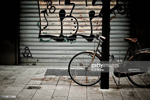 bicycle in front of tagged steel rolling shutter - industrial door stock pictures, royalty-free photos & images