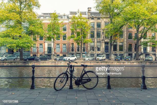 bicycle in herengracht canal, amsterdam - dutch culture stock pictures, royalty-free photos & images
