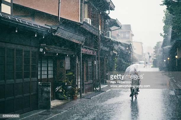 bicycle in the rain, takayama's old streets - 集中豪雨 ストックフォトと画像