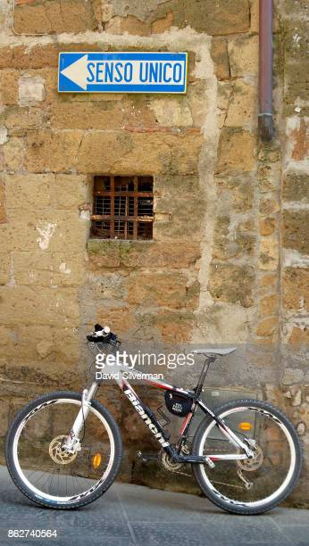 A bicycle is parked on a oneway street on July 22 2015 in the medieval village of Pitigliano in the Grosseto province of Tuscany Italy Tuscany is...