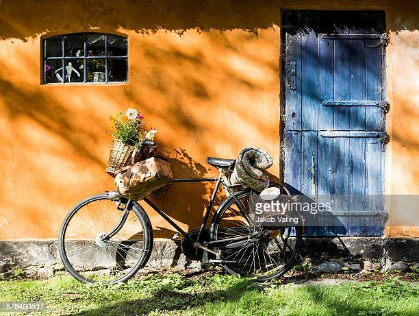 Bicycle leaning against cottaged wall with foraging baskets and wildflowers
