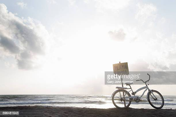 Bicycle leaning against sign on the beach