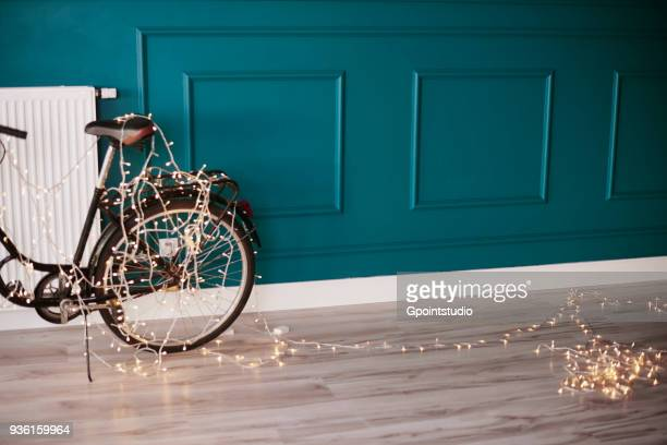 bicycle leaning against wall, indoors, decorated with fairy lights - ティール色 ストックフォトと画像
