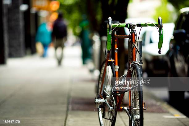 bicycle left on side of road in the city - racing bicycle stock pictures, royalty-free photos & images