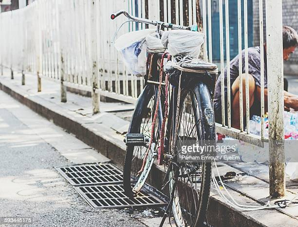 bicycle locked by railing on roadside - parham emrouz stock pictures, royalty-free photos & images