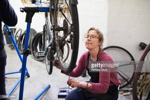 bicycle mechanic at work - biting lip stock pictures, royalty-free photos & images