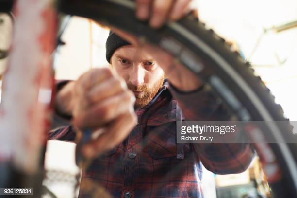 bicycle mechanic at work - bicycle shop stock pictures, royalty-free photos & images