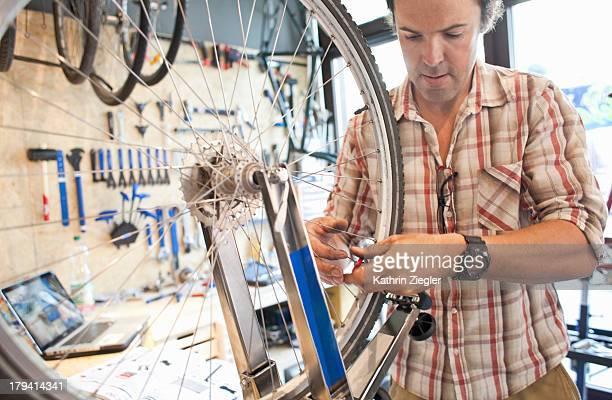 bicycle mechanic at work, truing wheel