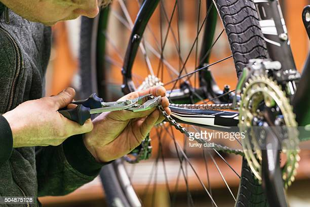 Bicycle mechanic repairing chain