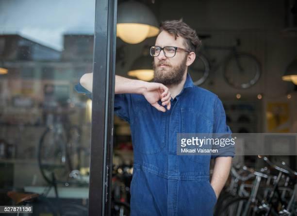 bicycle mechanic standing in bike shop - combinaison de protection photos et images de collection