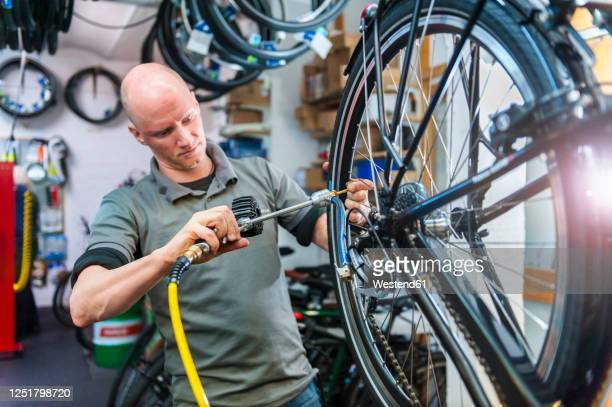 bicycle mechanic working in bike shop - inflating stock pictures, royalty-free photos & images