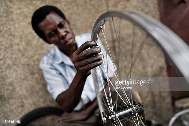 A bicycle mechanic works with a spoke wrench on bicycle wheel outside a small scale bicycle factory on June 27 2014 in Cali ColombiaDue to the strong...