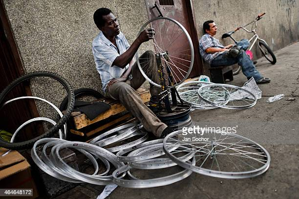 A bicycle mechanic works with a spoke wrench on bicycle wheel outside a small scale bicycle factory on June 27 2014 in Cali Colombia Due to the...