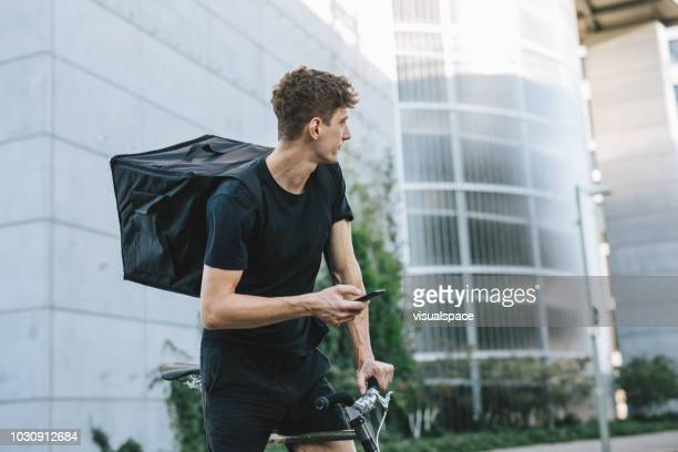 bicycle messenger checking directions on smartphone - bicycle messenger stock pictures, royalty-free photos & images