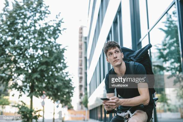 bicycle messenger checking directions on smartphone. - bicycle messenger stock pictures, royalty-free photos & images