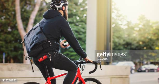 bicycle messenger: commuter with road bicycle in the city - bicycle messenger stock pictures, royalty-free photos & images