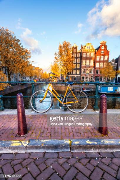 bicycle on a bridge in amsterdam - amsterdam stock pictures, royalty-free photos & images